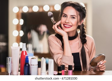 Cheerful female model doing makeup in dressing room