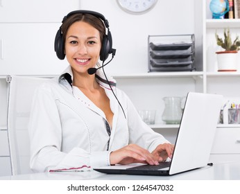 cheerful female operator with head set talking at customer service office