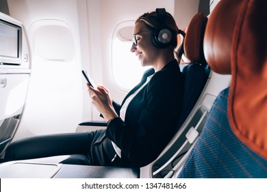 Cheerful female passenger in headphones for noise cancellation watching online movie during intercontinental flight in cabin of aircraft,happy young woman using wifi connection on board, playing games