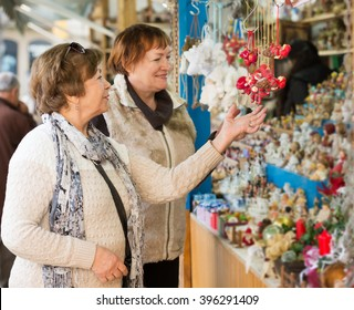 Cheerful female pensioners buying X-mas decorations at fair. Focus on left person