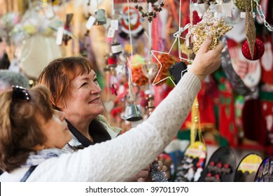 Cheerful female pensioners buying the X-mas decorations and souvenirs at fair