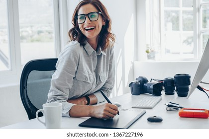 Cheerful female photographer working at her office desk. Woman with digital graphic tablet and drawing pen looking away and smiling.