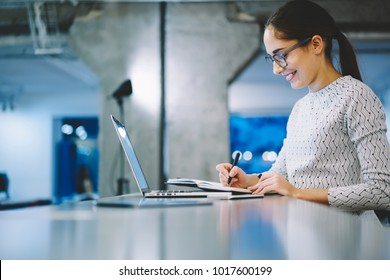 Cheerful female scientist satisfied with testing result noting information using laptop computer application during research, positive woman in laboratory happy about successful project results