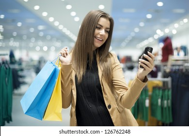 Cheerful female shopper reading a text on mobile phone