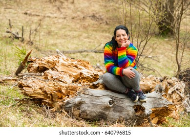 Cheerful female sitting on a bark tree in nature
