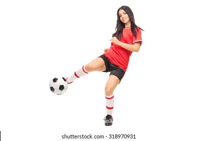 Cheerful female soccer player shooting a ball and looking at the camera isolated on white background