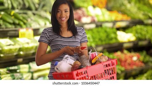 Cheerful female at supermarket holding basket smiling at camera