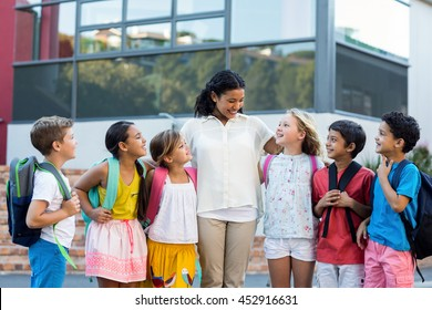 Cheerful female teacher with children standing outside school