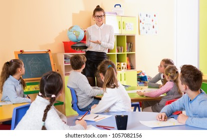 Cheerful female teacher giving geography lesson in classroom, showing pupils globe