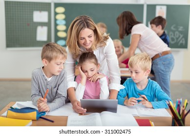 Cheerful Female Teacher with Kids Watching Something Educational Video on Tablet Computer Together Inside the Classroom.