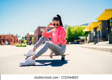 Cheerful female teenager in stylish sunglasses and streetwear resting at longboard during sport hobby in city, happy Asian hipster girl 20s enjoying recreation chill sitting at girlish skateboard
