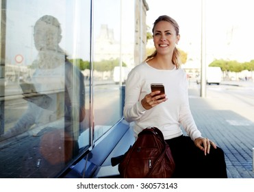 Cheerful female tourist using mobile phone for view map via network and continue her walk in strange city, beautiful hipster girl in good mood consult bus schedule via internet on her cell telephone