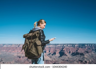 Cheerful female traveler with backpack using roaming data connection for blogging during wanderlust trip, smiling hipster girl satisfied with mobile network coverage connecting with friend on cellular