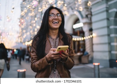 Cheerful female user with cellular technology in hand grinning at urban setting during evening walking, toothy hipster girl in classic eyewear for vision correction holding smartphone and laughing