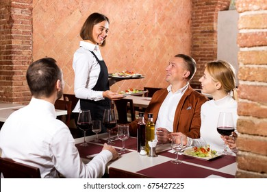 Cheerful female waiter carrying order for visitors in country restaurant