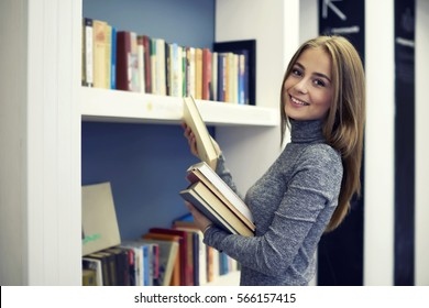 Cheerful female young professional librarian smiling while making revision of books putting them on new bookshelves in alphabetical order working in modern university library for pupils and students