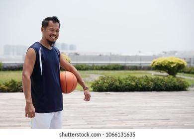 Cheerful Filipino man playing basketball outdoors