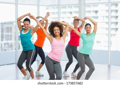 Cheerful fitness class and instructor doing pilates exercise in bright room