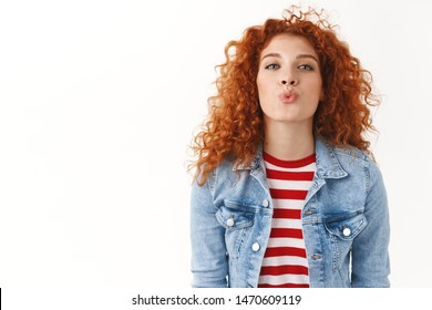 Cheerful flirty redhead caucasian girlfriend reaching camera give tender romantic muah folding lips waiting kiss passionately standing white background upbeat playful mood, finish date