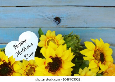 Cheerful floral with bright yellow silk sunflowers and a rustic blue washed plank background for Mother's Day in May. A heart shaped tag with Mother's Day greeting laying in the flowers.