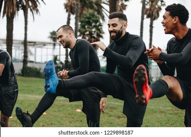Cheerful football players doing warm up exercises on the field before the match. Happy footballers doing leg raises standing on the field.
