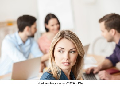 Cheerful four workers are talking in office