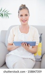 Cheerful fresh model in white clothes holding tablet pc sitting on cosy sofa