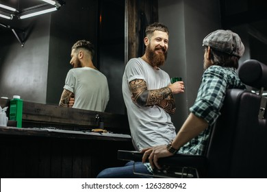 Cheerful friendly barber with long beard smiling and holding a glass while talking to his client