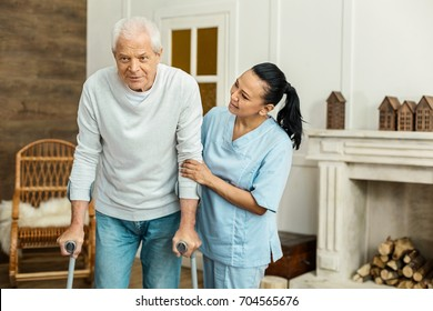 Cheerful friendly caregiver doing her job