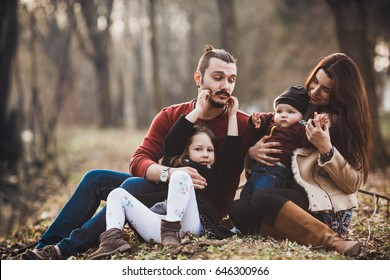 cheerful and friendly family resting on the river bank in the autumn park
