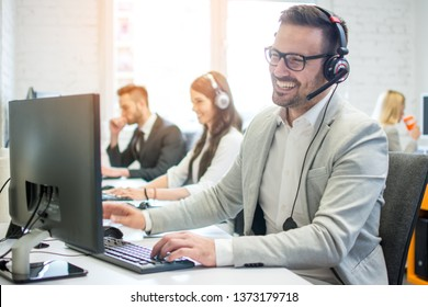 Cheerful friendly online technical operator agent with headphones and microphone talking with client in customer support office