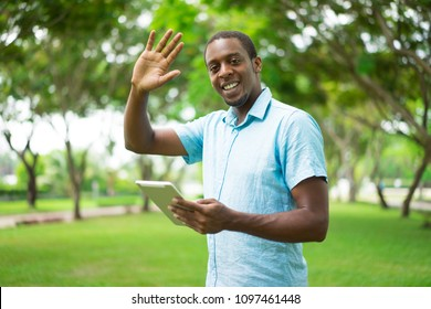 Cheerful friendly young African man with tablet waving hand