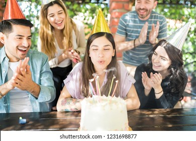 Cheerful friends clapping for birthday woman blowing candles on cake at restaurant