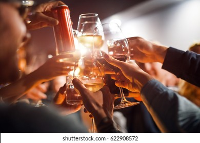 Cheerful friends clinking glasses above dinner table. Alcohol and toasting, party and celebration theme. Congratulations on the event.