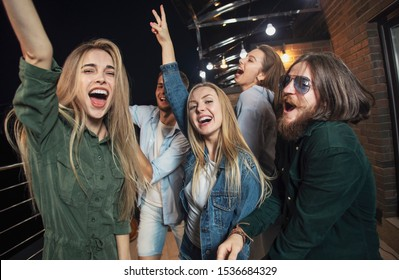Cheerful friends dancing all night long during their party on a loft balcony