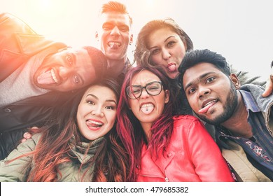 Cheerful friends from different countries and races taking selfie with back lighting - Happy youth concept with young people having fun together - Main focus on bottom guys - Vintage retro filter