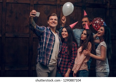 Cheerful friends do birthday selfie. Handsome man with a tatoo holds a phone to make selfie of himself anf his friends at his birthday party