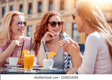 Cheerful friends drink coffee,having fun outdoors. Dating, consumerism, food and lifestyle concept.