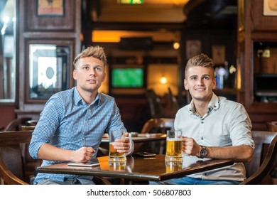 Cheerful friends drinking beer in pub and looking in tv screen