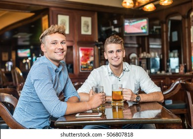 Cheerful friends drinking beer in pub and looking into camera.