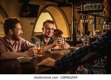 Cheerful friends drinking draft beer in a pub