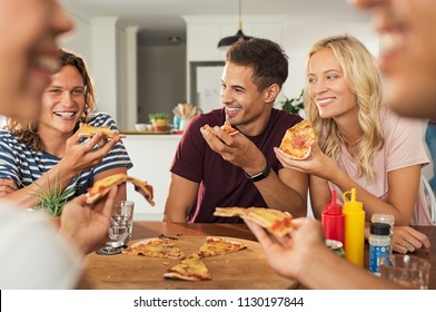 Cheerful friends enjoying pizza together at home. Happy smiling men and young women sharing pizza for dinner. Group of multiethnic guys and girls having party and eating sitting around the table.