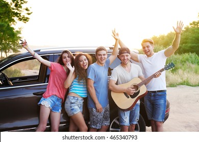 Cheerful friends with guitar near car, outdoors