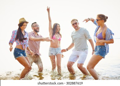 Cheerful friends having fun in water during vacations