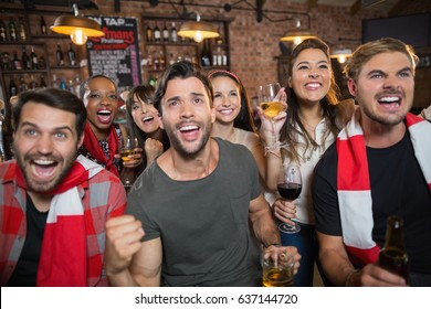 Cheerful friends holding drinks while enjoying in pub