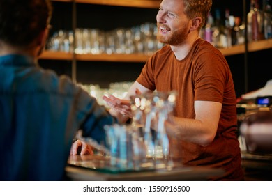 Cheerful friends leaning on bar counter, drinking beer and chatting with bartender. Night out.
