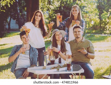 Cheerful friends on picnic in the park. Eating pizza.