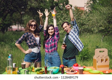 Cheerful friends outdoors next to picnic table. Three young freinds raising their hands up and shouting standing behind table full of food.