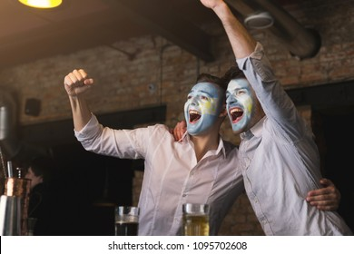 Cheerful friends with painted faces emotionally watching soccer game in sport bar. Holiday, leasure, football fans concept