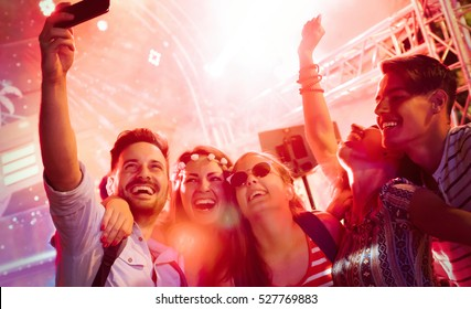 Cheerful friends partying in club at night